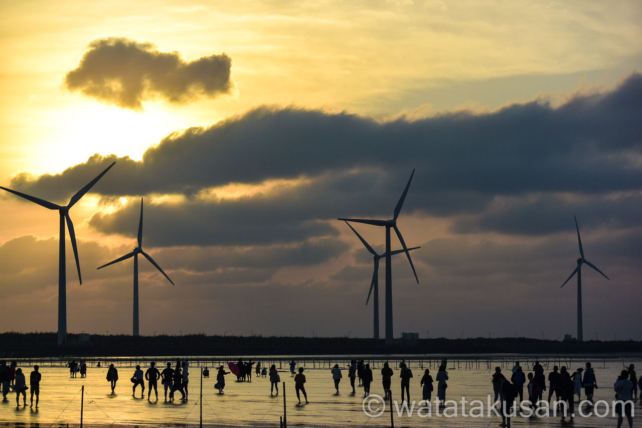 台湾の夕日と風車と人